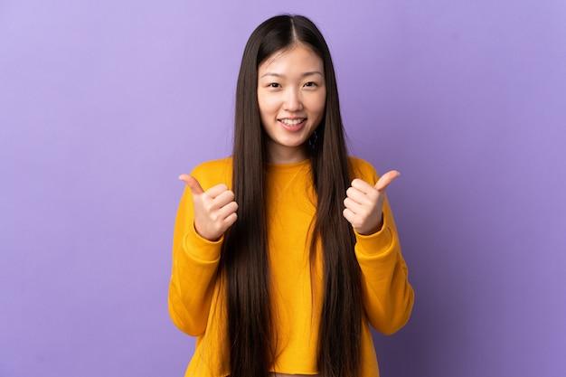 ジェスチャーと笑みを浮かべて親指で孤立した紫色の壁を越えて中国の少女