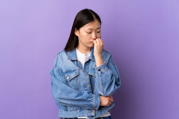 Молодая китайская девушка над изолированной фиолетовой стеной имея сомнения