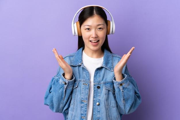 Молодая китайская девушка над изолированной фиолетовой стеной удивленная и слушая музыка