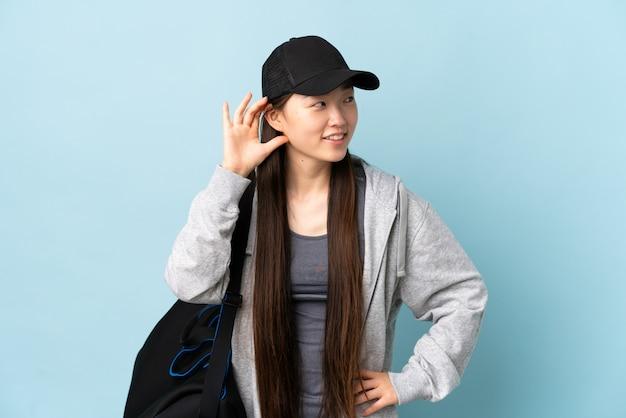 Молодая спортивная китаянка со спортивной сумкой над изолированной синей стеной слушает что-то, положив руку на ухо