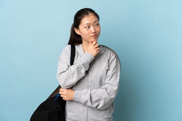 Молодая спортивная китайская женщина со спортивной сумкой на изолированной синей стене, обдумывающая идею, глядя вверх