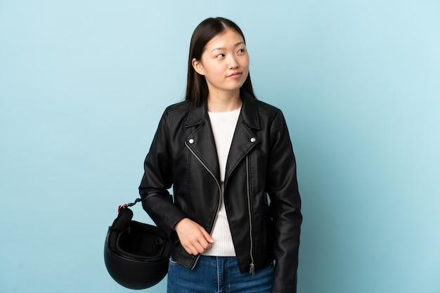立っていると側にいる孤立した青い壁にオートバイのヘルメットを保持している中国の女性