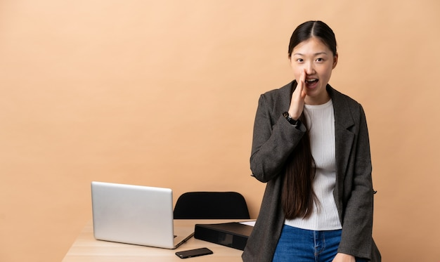 Китайская деловая женщина на рабочем месте кричит с широко открытым ртом