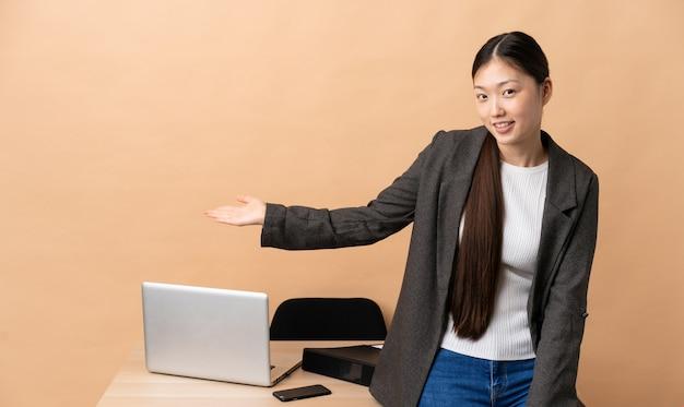 Китайская деловая женщина на рабочем месте, протягивая руки в сторону за приглашение прийти
