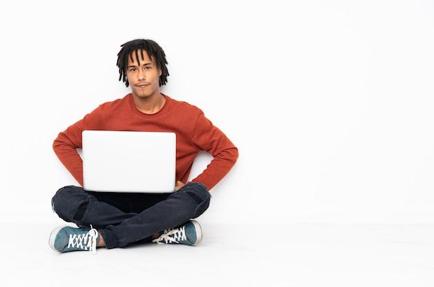 床に座って怒っている彼のラップトップで働く若いアフリカ系アメリカ人