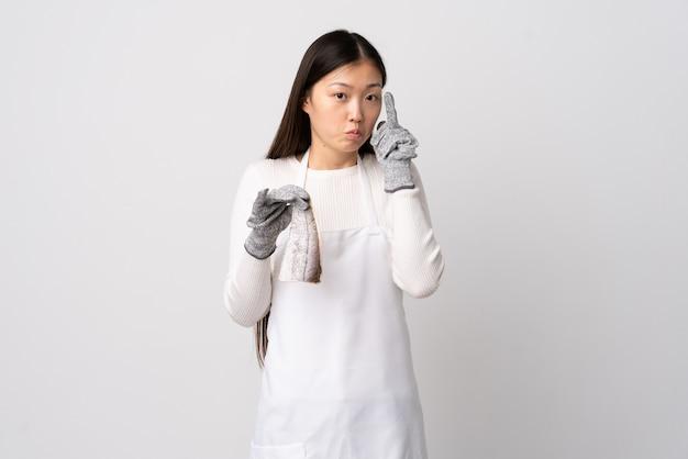 Китайский торговец рыбой, носящий фартук и держащий сырую рыбу над изолированной белой стеной, обдумывающий идею