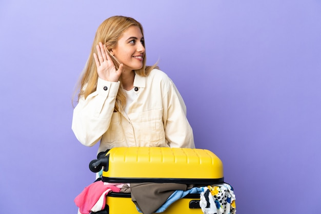 Молодая уругвайская белокурая женщина с чемоданом, полным одежды над изолированной фиолетовой стеной, слушает что-то, кладя руку на ухо