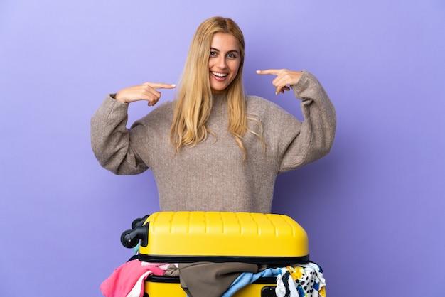 親指ジェスチャーを与える分離の紫色の壁に服の完全なスーツケースを持つ若いウルグアイブロンドの女性