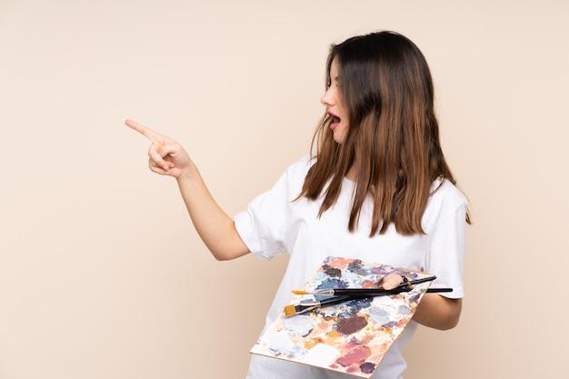孤立した壁の上の若い画家女性