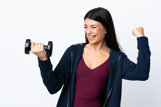 勝利を祝っている白い壁に重量挙げを作る若いスポーツ女性