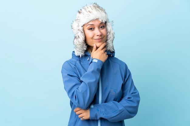 Молодая девушка в зимней шапке на синей стене смеется
