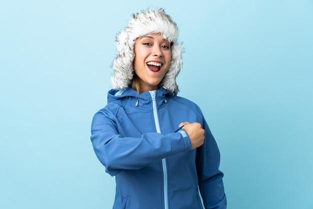 Молодая девушка в зимней шапке на синей стене празднует победу