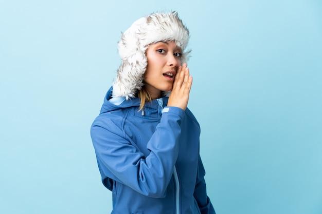 Молодая девушка в зимней шапке на синей стене шепчет что-то