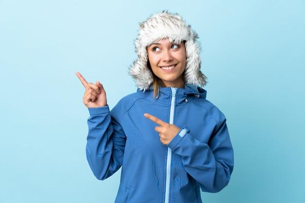 Маленькая девочка с шляпой зимы на голубой стене указывая с указательным пальцем отличная идея