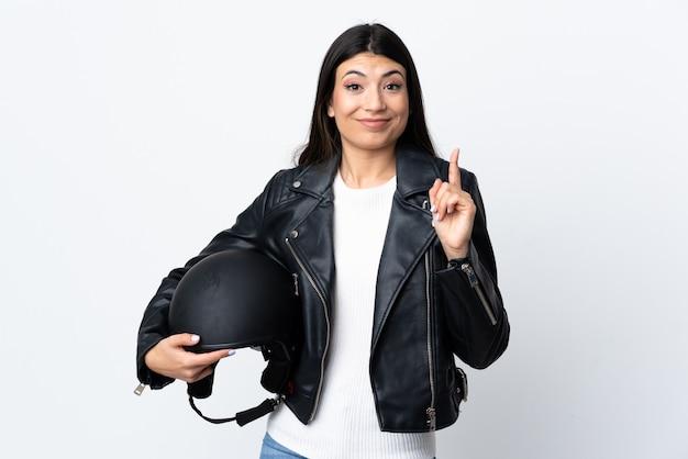 人差し指で指している白い壁にオートバイのヘルメットを保持している若い女性の素晴らしいアイデア