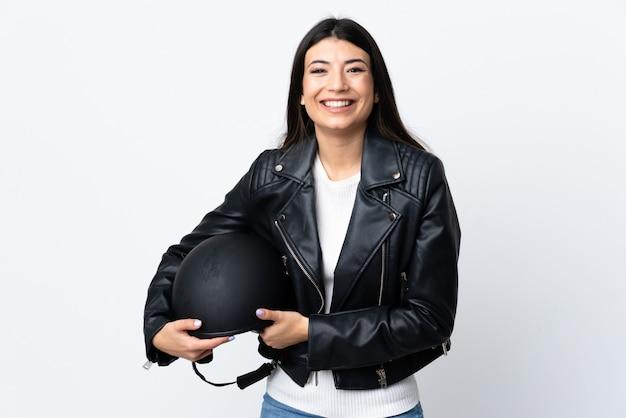 白い壁の笑いにオートバイのヘルメットを保持している若い女性