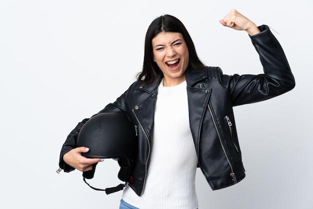 勝利を祝っている白い壁にオートバイのヘルメットを保持している若い女性