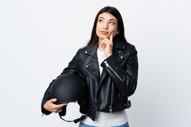 アイデアを考えて白い壁にオートバイのヘルメットを保持している若い女性