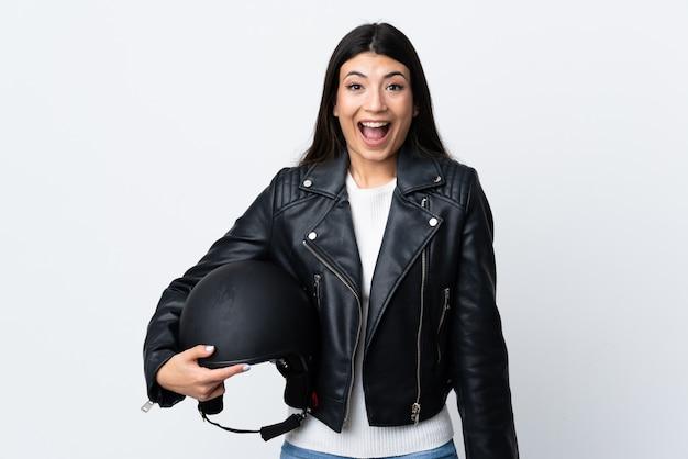 驚きの表情で白い壁にオートバイのヘルメットを保持している若い女性