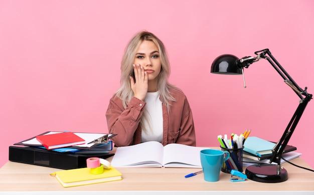 Молодая женщина студента работая в таблице несчастной и расстроенной