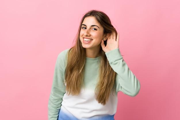 Молодая женщина за розовой стеной, слушая что-то, положив руку на ухо