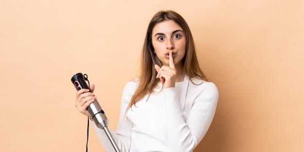 壁にハンドブレンダーを使用して、口の中に指を入れて沈黙のジェスチャーの兆しを見せている女性