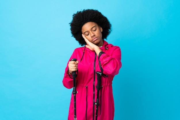 Молодой афроамериканец с рюкзаком и треккинговыми палками на синей стене делает жест сна в достойном выражении