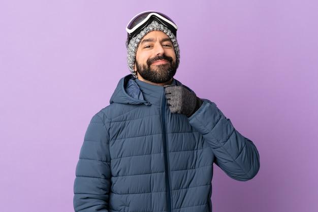 Лыжник в сноубордических очках над фиолетовой стеной