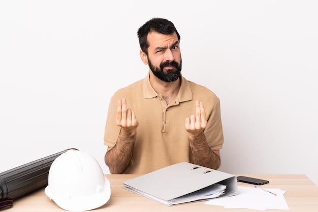 お金のジェスチャーを作るテーブルでひげを持つ白人建築家男が台無しに