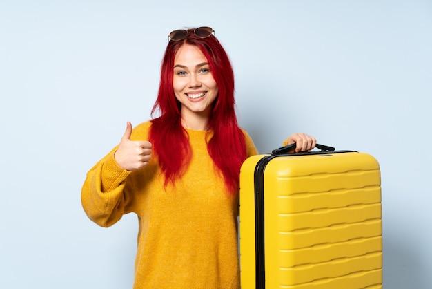 手のひらに架空の空白スペースを保持している青い壁にスーツケースを持って旅行者の女の子が広告を挿入し、親指を立てる