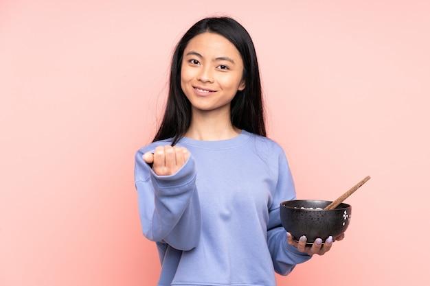 Женщина подростка азиатская на бежевой стене приглашая прийти с рукой. рад, что вы пришли, держа миску лапши с палочками для еды
