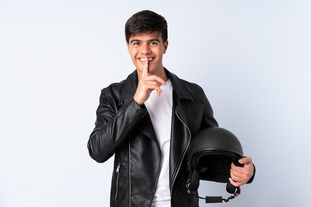 沈黙のジェスチャーをしている青い壁の上のオートバイのヘルメットを持つ男