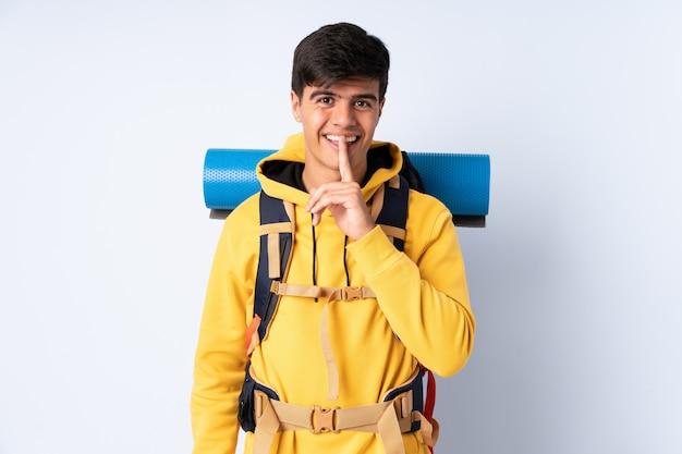 沈黙のジェスチャーをしている青い壁に大きなバックパックを持つ若い登山家男