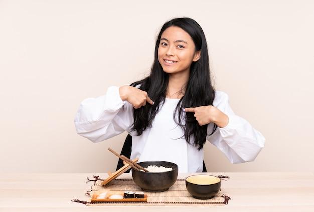 Девушка подростка азиатская есть азиатскую еду на бежевой стене с выражением лица сюрприза