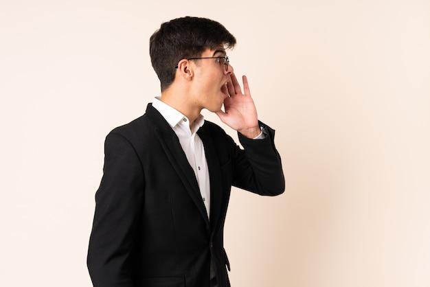 Бизнесмен на бежевой стене кричит с широко открытым ртом