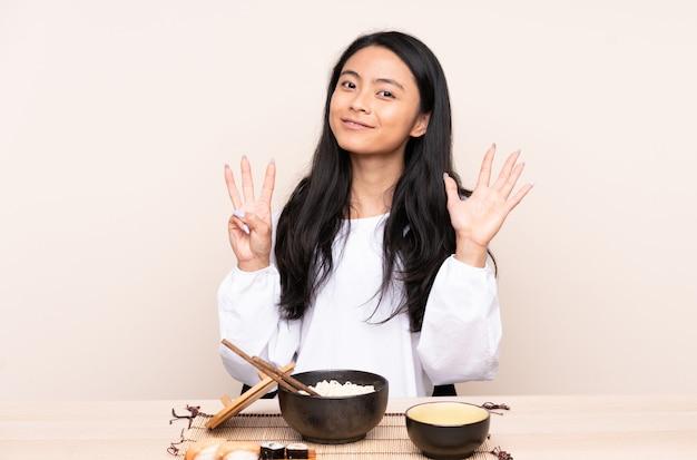 Девушка подростка азиатская есть азиатскую еду на бежевой стене подсчитывая восемь с пальцами