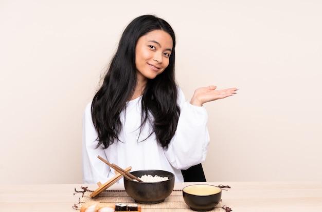 Девушка подростка азиатская есть азиатскую еду на бежевой стене представляя идею пока смотрящ усмехающся к