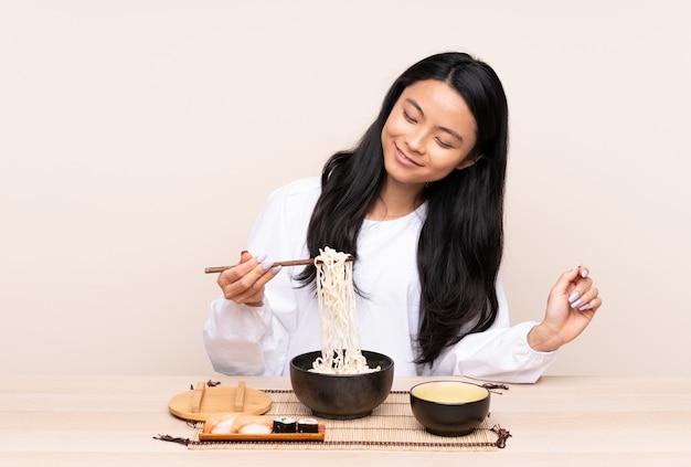 Девушка подростка азиатская есть азиатскую еду на бежевой стене