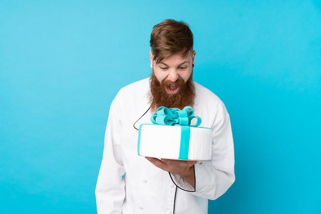 水色の壁に大きなケーキを持って長いひげと赤毛のパティシエ
