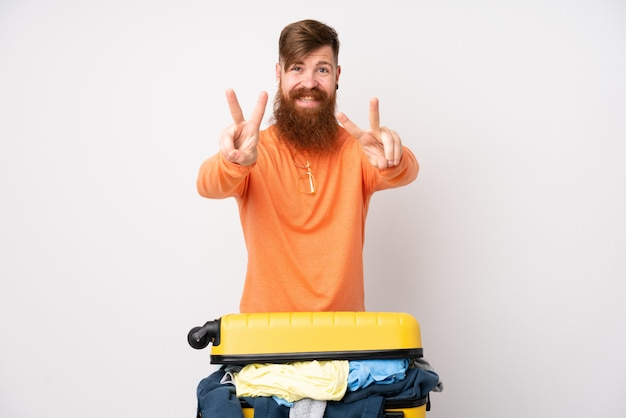 Человек путешественника с чемоданом, полным одежды над белой стеной, улыбается и показывает знак победы