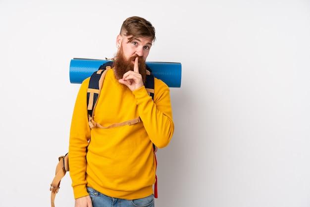 沈黙のジェスチャーをしている白い壁に大きなバックパックを持つ若い登山家男