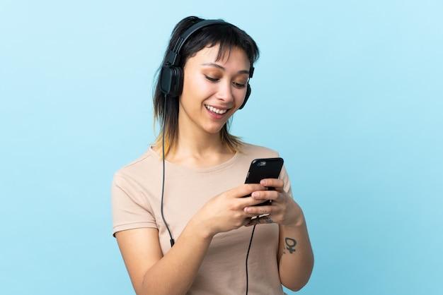 Молодая уругвайская девушка над синей стеной слушает музыку и смотрит на мобильный