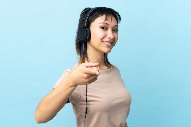 Молодая уругвайская девушка над синей стеной слушает музыку и указывает на фронт