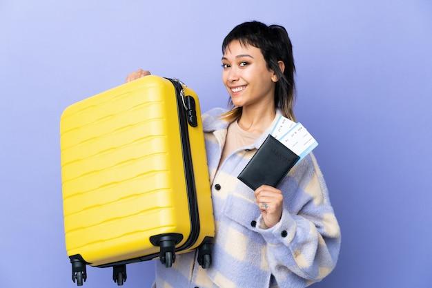 Молодая уругвайская женщина над фиолетовой стеной в отпуске с чемоданом и паспортом