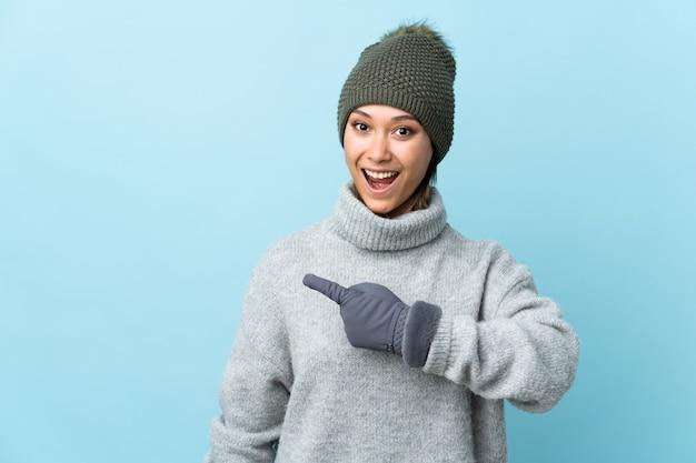 Молодая уругвайская девушка в зимней шапке на синей стене указывает пальцем в сторону