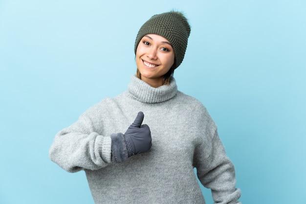 Молодая уругвайская девушка с шляпой зимы на голубой стене давая жест больших пальцев руки вверх