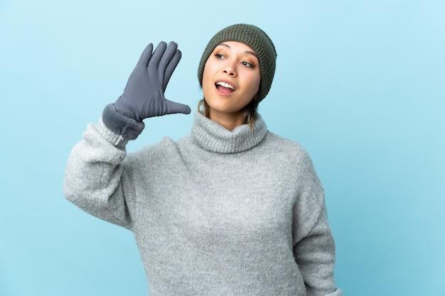 Молодая уругвайская девушка в зимней шапке на синей стене кричит с широко открытым ртом