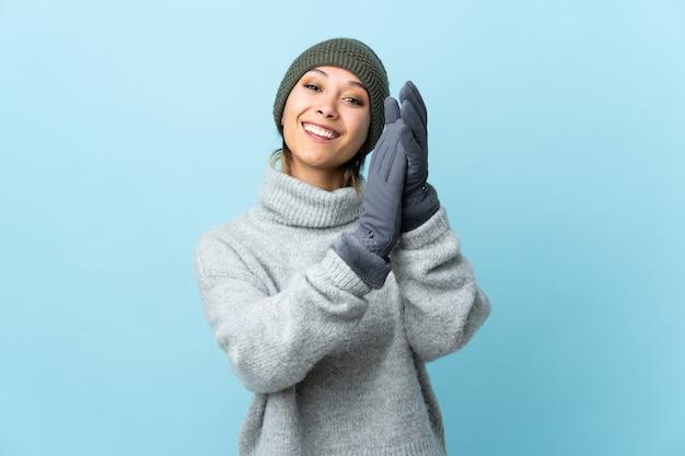 Молодая уругвайская девушка в зимней шапке на синей стене аплодирует