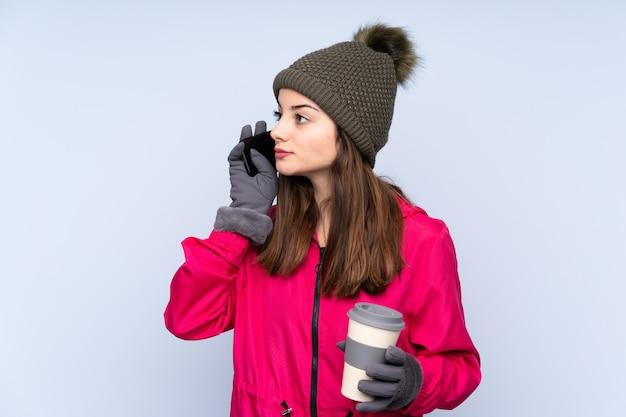 Молодая девушка в зимней шапке на синей стене держит кофе и мобильный телефон