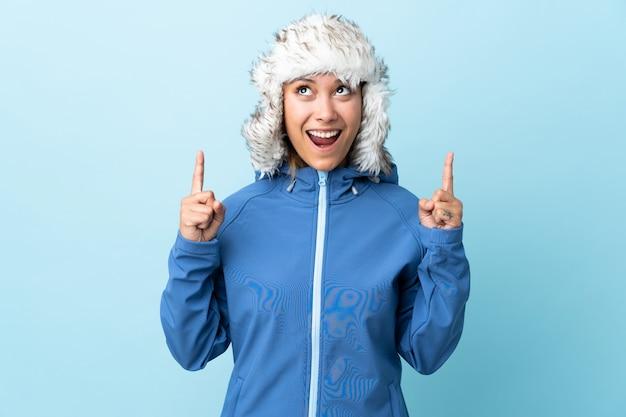 Молодая уругвайская девушка в зимней шапке на синей стене показывает указательным пальцем отличную идею